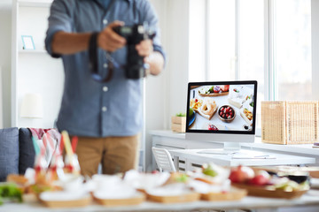 Mid section portrait of unrecognizable photographer taking picture of table with food, focus on computer screen in background, copy space