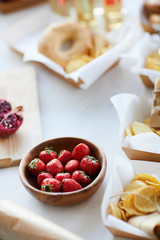 High angle background of rustic table with delicious strawberries in wooden bowl and various snacks for party, copy space