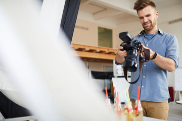 Waist up portrait of smiling male photographer shooting objects and food in photo studio, copy space