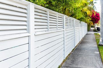 White fence and red or pink bougainvillea flowers in Florida Keys or Miami, green plants landscaping landscaped sidewalk street road house during summer spring day