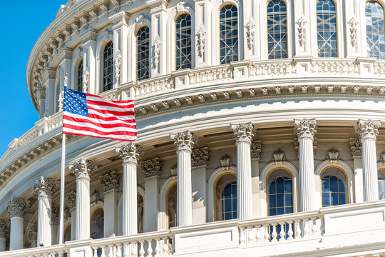 US Congress dome closeup with American flag waving in Washington DC, USA on Capital capitol hill, blue sky, columns, pillars, nobody