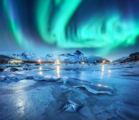 Tuinposter Noorderlicht Northern lights above snowy mountains, frozen sea coast and houses in Lofoten islands, Norway. Aurora borealis and small village. Winter landscape with polar lights, rorbu, ice. Aurora over rocks