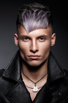 Young man with purple hair and creative makeup and hair.