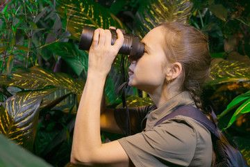 traveler girl among the tropical forest looks into the distance through binoculars