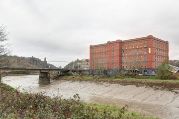The Avon river with mud after a storm, next to a red brick abandoned industrial building and a bridge in a cloudy winter in Bristol, United Kingdom