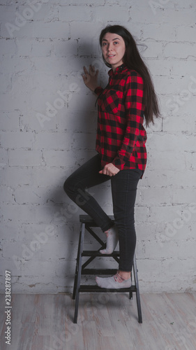 5b1a002a7c7e1e The girl in the red black plaid shirt. Brunette posing with a chair, against