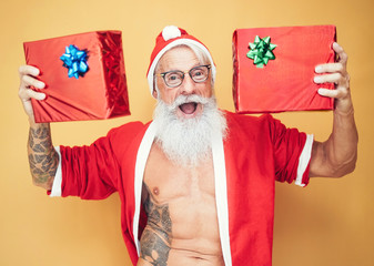Tattooed fit santa claus holding christmas gifts - Trendy bearded hipster senior wearing xmas clothes showing presents - Concept of celebration culture and x-mas holidays concept