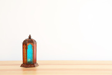 Muslim lantern Fanous on table against light background. Space for text