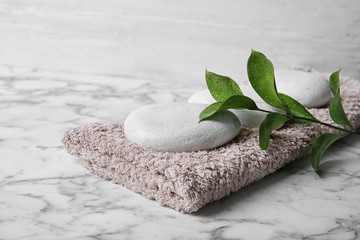 Beautiful composition with spa stones and towel on table