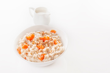 Oatmeal with pumpkin and nuts in a plate and a jug with milk on a white background. Close-up. Copy space
