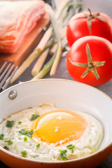 Fried egg in a pan, sliced bread, bacon, tomatoes and green onions cooked for breakfast on a wooden gray table. Close-up