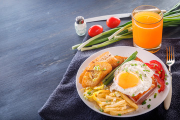Fried egg with bacon in a white plate with fried pieces of bread, greens, tomatoes, french fries and a glass of fresh juice on a gray wooden table. Close-up. Copy space
