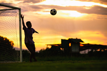An action sport picture of a kids playing soccer football as a goalkeeper for exercise in community rural area under the sunset.