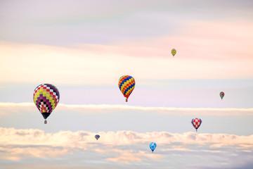 朝陽と彩雲を背景に飛ぶ複数の熱気球。希望、夢、ノンビリ、スローイメージ