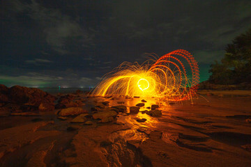 .cool burning steel wool art fire work photo experiments on the beach at sunset