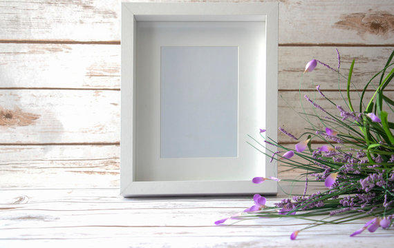 5x7, 8x10 white frame with wild flowers on a white wood background.