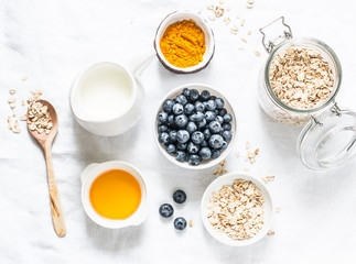 Ingredients for cooking coconut milk turmeric blueberry oatmeal porridge on a light background, top view. Gluten free, vegetarian food concept