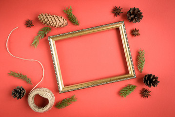 Christmas composition of gift box, fir branches, cones, red bow on red background.