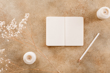 Open notebook with white pencil among white flower plant, pencil and candles. Flat lay, top view, cmock up. The concept of planning and goals to set on New Year.