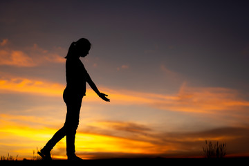 Silhouette of sad and depressed women walking at walkway of park with sunset