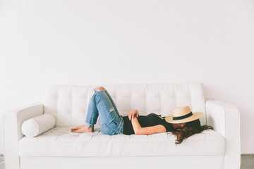 Fototapeta A beautiful young woman relaxing on a white couch with a hat covering her face. obraz