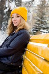 beautiful woman in yellow knitted hat and blue leather jacket sitting on a bench outdoor in winter
