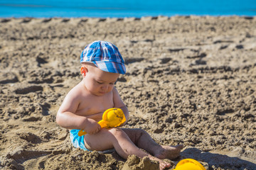 One year old kid playing on the beach at the summer day time.