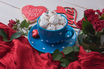 Romantic breakfast on valentine's day. Blue cup of hot beverage with biscuits and red roses on a white wooden table. Morning surprise for lovers. Top view.