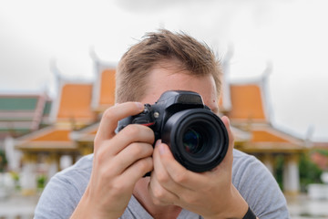 Tourist man photographing with camera against view of the Buddhist temple in Bangkok