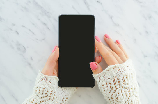 Woman hands holding smartphone on marble background with copy space. Flat lay. Top view. Woman using mock up mobile phone with top view.