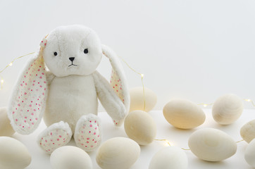 Cute white rabbit bunny toy and wooden decorative eggs. Bright Easter mockup background with copy spaces. Happy Easter eggs concept
