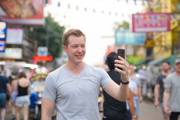 Young happy tourist man taking selfie against view of busy street in Khao San in Bangkok