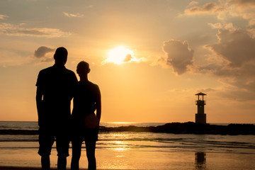 Happy couple on the beach during sunset time