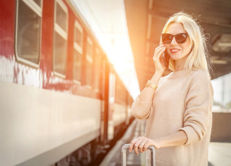 Blonde woman with her luggage stay  and speak in her mobile near train