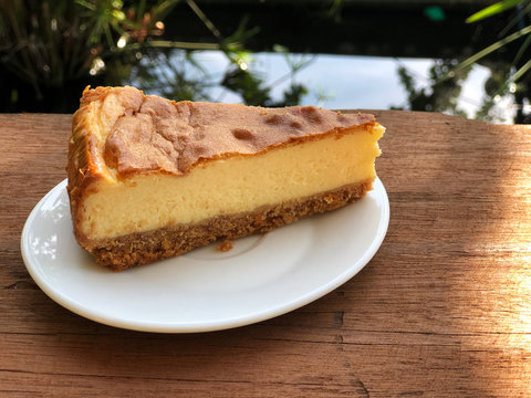 New York  cheese cake in white dish on the wooden table with sunlight . Homemade bakery.