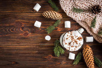 Mug with hot drink with marshmallow, chocolate bars and knitted scarf on dark wooden background