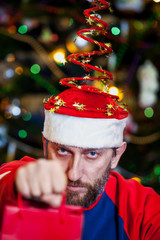 Man with beard in Christmas hat on background of tree
