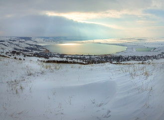 Winter lake in the snow. Lake snowy winter with clouds. Top view of the lake.