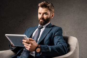 confident businessman holding digital tablet and sitting in armchair