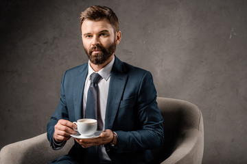 serious businessman sitting in armchair with cup of coffee