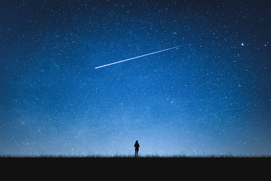 Silhouette of girl standing on mountain and night sky with shooting star. Alone concept.