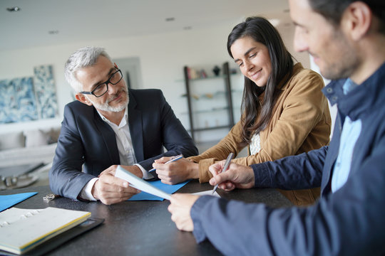 Attractive couple signing contract with real-estate agent in contemporary house