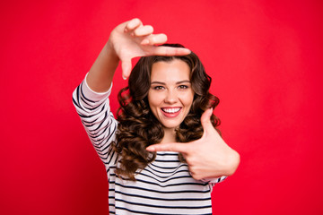Close up portrait of glad attractive young she her woman with beaming smile making frame with thumbs and forefingers looking through camera isolated on red vivid bright background