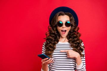 Portrait of nice funky childish attractive positive wavy-haired lady in striped pullover eyeglasses eyewear sunhat showing sms opened mouth isolated over bright vivid shine red background
