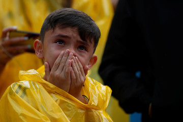 A Colombian fan reacts while watching the broadcast of the World Cup Round of 16 soccer match between Colombia and England in Bogota