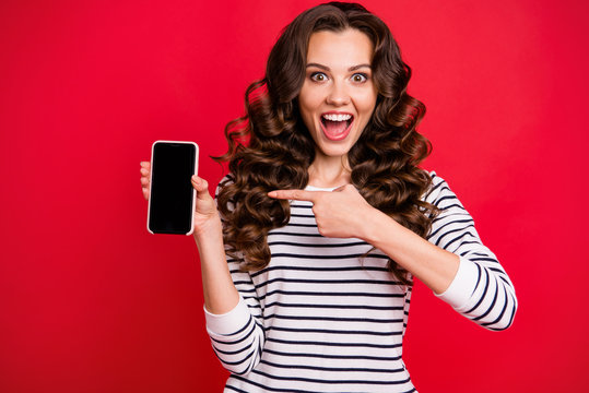 Portrait of nice cute crazy funny attractive amazed wondered stunned wavy-haired lady wearing striped pullover pointing at black screen display isolated over bright vivid shine red background