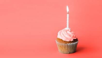holiday, celebration, greeting and party concept - birthday cupcake with one burning candle in trendy color of the year 2019 living coral