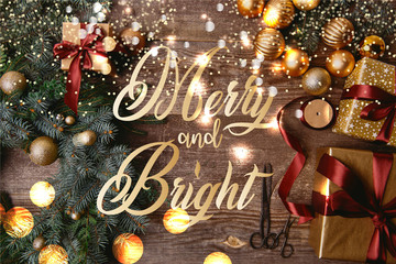 """elevated view of Christmas gift boxes, fir wreath, ribbon spool and scissors on wooden table with """"merry and bright"""" lettering and glowing lights"""