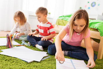 childhood, leisure and people concept - happy kids with paper, crayons and washi tape making crafts at home