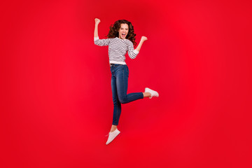 Full length size body portrait of jumping high beautiful pretty charming she her girl raised hands wearing white striped casual sweater and jeans on red vivid bright background